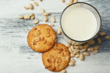 Peanut cookies with milk on wooden background