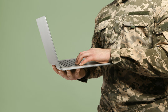 Soldier with laptop on grey background, closeup