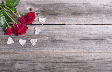 Red roses and heart on a wooden background.