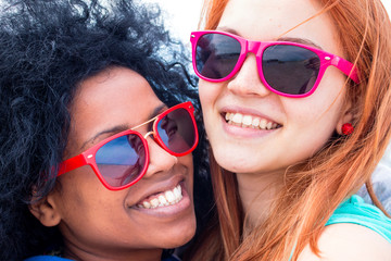 best friends together. 2 fashionable girls, afro hair girl with blond girl smiling for a selfie photo