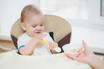 mother feeding her baby breast porridge day