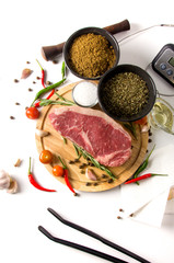 raw steak cutting board spices top view