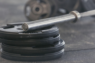 Disassembled barbell on floor in gym, close up
