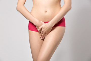 Close up view of young woman on grey background. Gynecology concept
