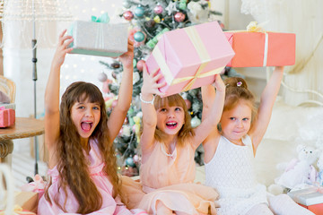 Three young happy girls with Christmas gifts