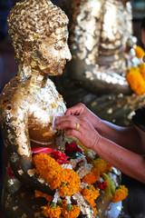 Attach gold leaf on Buddha statue , Buddism make merit by using gold leaf to worship the buddha