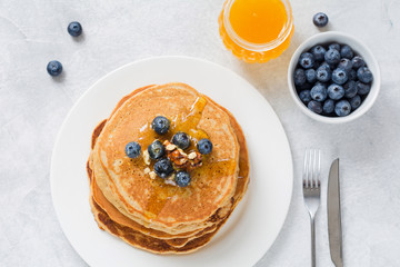 Stack of pancakes with fresh blueberries, nuts and honey on white plate. Healthy breakfast food. Table top view