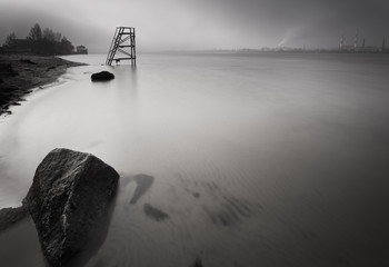 Lifeguard tower on the late autumn beach. Big stone in the water on foreground. Long exposure shot. Kiev. Ukraine.