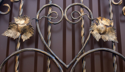 Forged metal fence with decorative elements in the form of gold leaf
