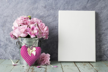 Pink carnation flower in zinc bucket and blank canvas frame on v