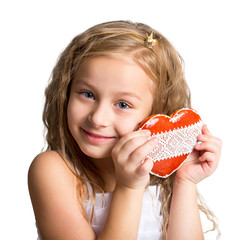 Portrait of a beautiful little girl with gingerbread heart-shaped. Photo a child closeup on a white background