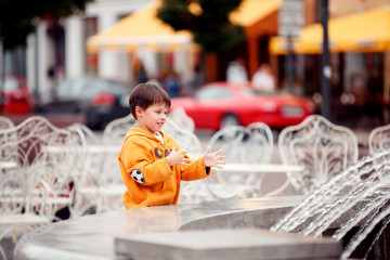 Cute little boy playing with a city fountain