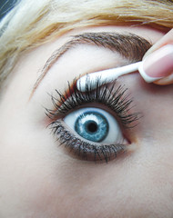 Women's eye is drawn with a cotton swab and finger French manicure. macro