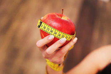 Closeup on measuring apple in caucasian woman`s hands.