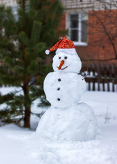 Snowman in a red cap of Santa Clau