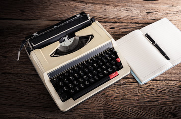 Vintage typewriter and a blank notebook and pen