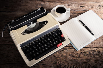 Vintage typewriter and a blank notebook , pen and coffee cup