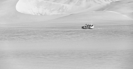 Tourists travel through the dunes in the Atacama Desert - Oasis of Huacachina, Peru, South America (black and white)