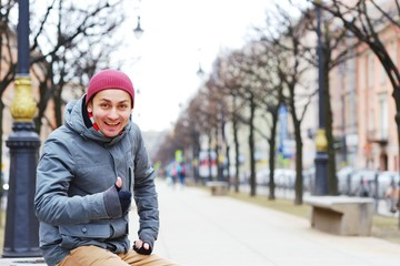 Young cheerful man in warm jacket sitting on a bench in the alley in center St. Petersburg and fun laughs.
