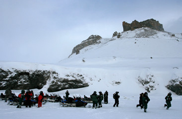 The group of tourists with snowmobiles stop near the mountain.