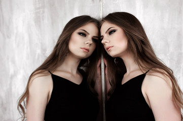 Young girl with long beautiful hair and smoky eyes wearing black maxi evening dress posing with a mirror. Studio shot