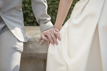 Clasped hands of the bride and groom with rings