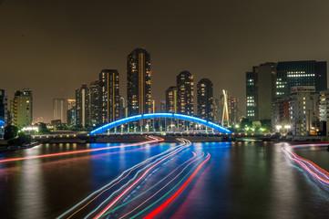 隅田川の夜景:高層ビルと行き交う船の光跡