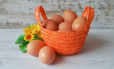 Eggs in orange wicker basket on a white wooden background