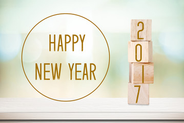 Wooden cubes with 2017 and happy new year over blur background