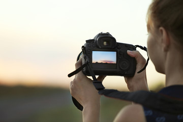 Woman with camera on natural blurred background