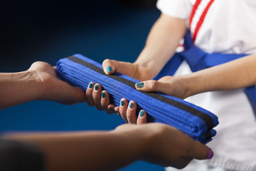 Karate Belt Promotion. Teacher handing belt to youth student. Shallow Depth of Field, focus is on the belt.