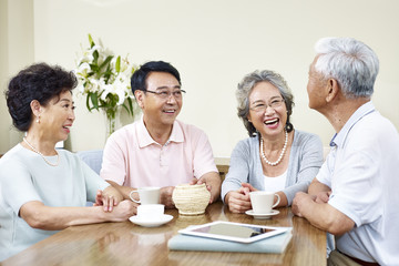 senior asian friends relaxing chatting at home