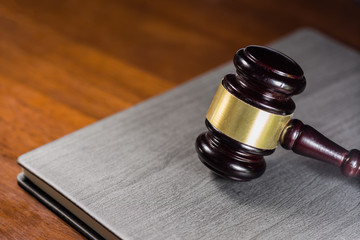 Law gavel on black leather cover book