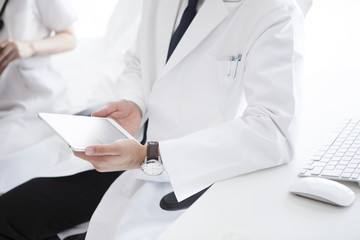 Male doctor is using electronic tablet