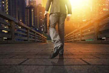 Young manager carrying a briefcase while walking on the road / bridge toward a city