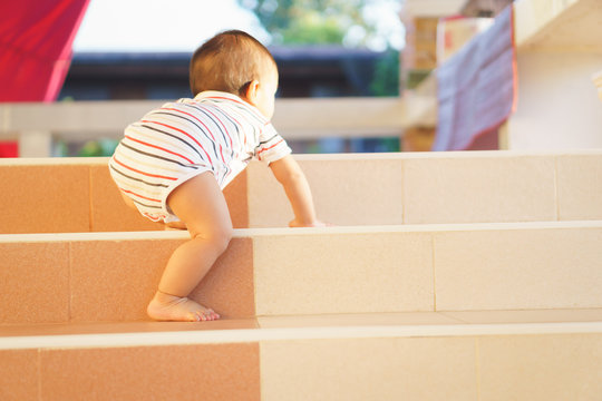 10 months adorable Asian baby climbing down stairs