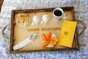 """Breakfast with eggs and coffee on a wooden tray with inscription """"good morning"""". Tablecloth with fish. Yellow envelope"""