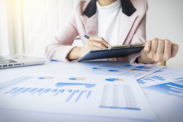 Portrait of business woman with laptop, finance graph and writes