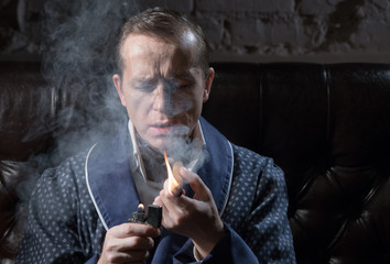 Man in an elegant dressing gown smoking a Cuban cigar and drinking alcohol