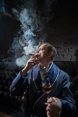 Man in his office smoking a cigar and drinking brandy