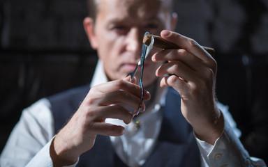 man cuts a cigar