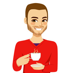 Happy attractive young man drinking hot coffee