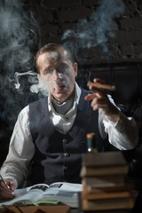 A man smokes a cigar and the smoke released from the mouth