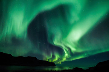 Northen lights (Aurora Borealis) in Iceland over the fjord