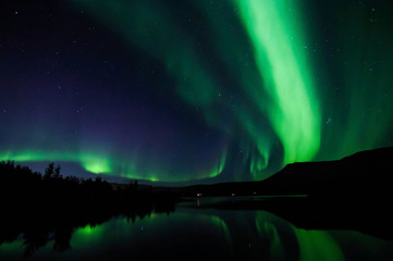 Northen lights (Aurora Borealis) in Iceland with mirroring on the lake