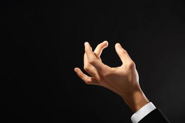 Male hand holding something on dark background