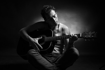 Young caucasian man play a acoustic guitar. Black and white picture, low key studio portrait