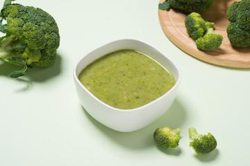Tasty broccoli soup on a green background