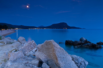 Rocks and sandy beach under the moon shine after twilight, Sithonia, Greece