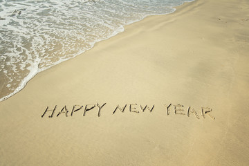 happy new year written in sand write on tropical beach